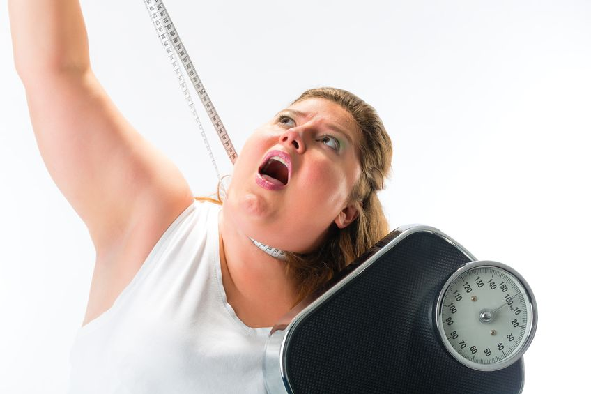19000693 - obese woman strangling herself with measuring tape and holding a weight scale