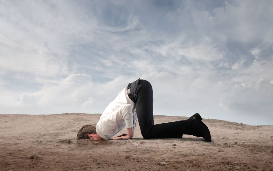 13638557 - young businessman burying his head in the sand